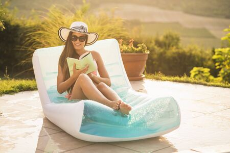 Attractive young woman wearing bikini, sunglasses and a hat, lying on an air matress by the swimming pool, sunbathing and reading a book