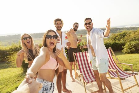 Group of young friends having fun at a poolside summertime party, drinking beer and inviting more friends to join them Stock Photo