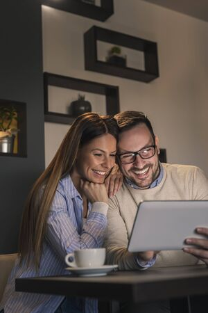 Beautiful young couple sitting at a restaurant table, drinking coffee and using a tablet computer Imagens