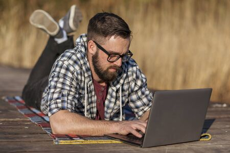 Male freelancer lying on the lake docks, working remotely while relaxing in nature