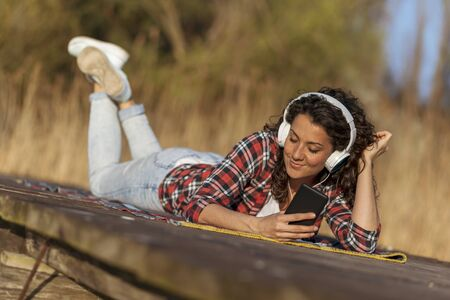 Woman lying on the lake docks, relaxing after a long day of hiking in nature, listening to the music Stock Photo