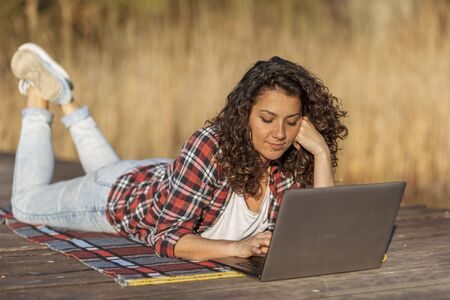 Female blogger lying on the lake docks, writing a travel blog post while relaxing in nature