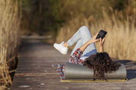 Woman lying on the lake docks, relaxing after a long day of hiking in nature, using a smart phone Stock Photo