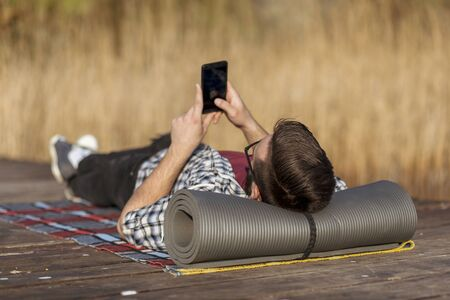 Man lying on the lake docks, relaxing after a long day of hiking in nature, using a smart phone