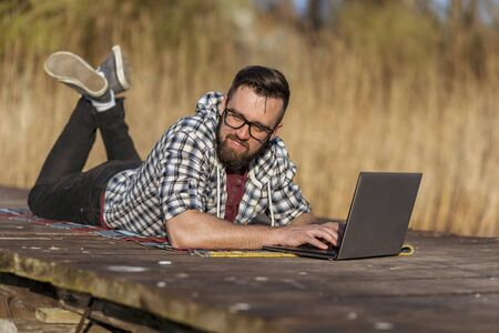 Man lying on the lake docks, using a laptop computer, working remotely while relaxing in nature Stock Photo