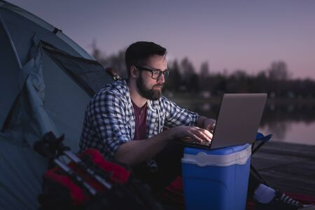 Man camping by the lake, sitting on the tent entrance and working on a laptop computer;  digital nomad lifestyle