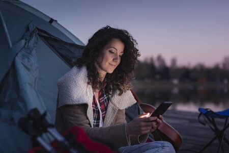 Beautiful young woman camping on the lake docks, sitting near the tent entrance and typing a text message