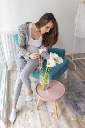 Beautiful pregnant woman sitting in an armchair near the window, putting calla lillies flower bouquet into a vase and relaxing at home