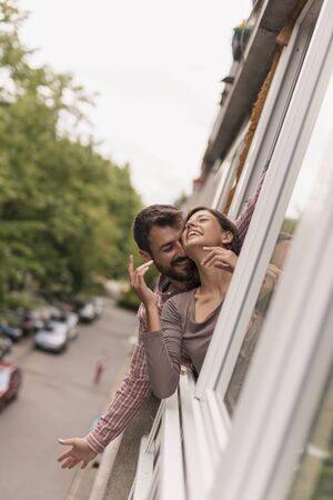 Beautiful young couple in love leaning through an opened window, looking outside on the street, smiling and hugging