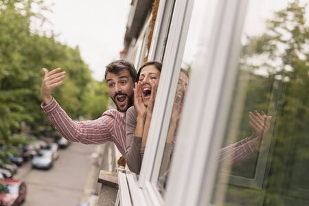 Beautiful young couple leaning through an opened apartment window, waving and shouting, calling friends passing by in the street