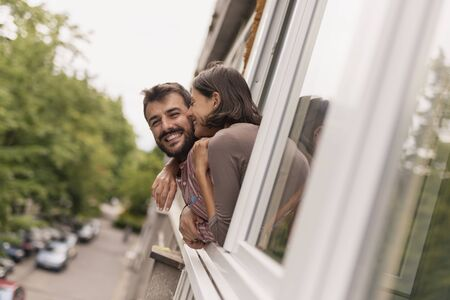 Beautiful young couple in love leaning through an opened window, looking outside on the street, smiling and hugging Stockfoto - 127979554