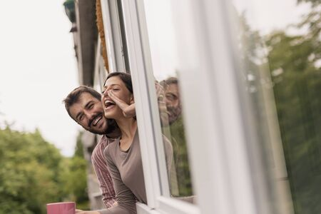 Couple leaning through an opened window, drinking coffee and calling friends passing by Stockfoto - 127979552