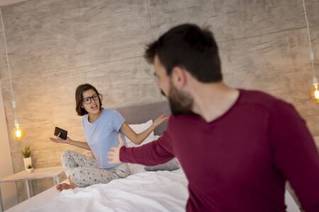 Young couple wearing pajamas, sitting on bed and having a fight early in the morning in bedroom Stockfoto - 127979555
