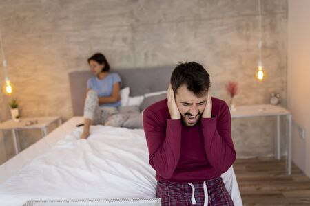 Couple having an arguement in bedroom, shouting at each other, man holding head in hands and covering ears Stockfoto - 127979558