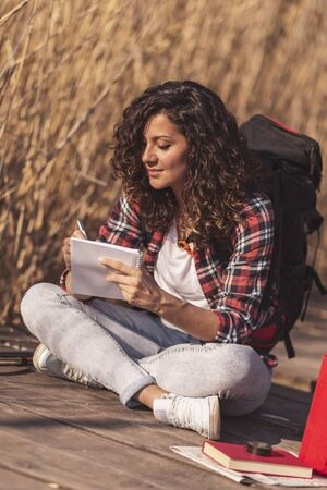 Young female biologist wearing a backpack sitting on wooden lake docks on a sunny autumn day, taking notes while on field work trip