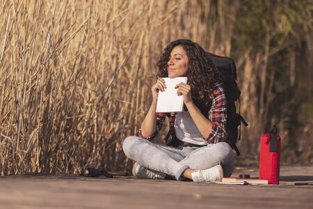 Beautiful young woman sitting on the wooden lake docks, enjoying a sunny autumn day in nature, holding a notebook, pensive and relaxed Stockfoto - 127979654