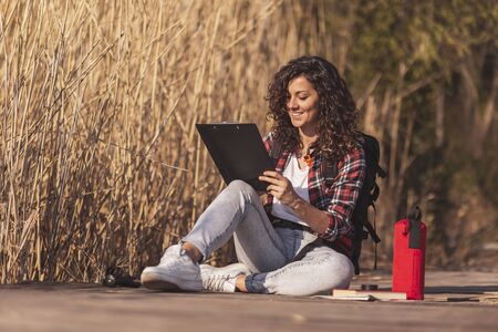 Female artist sitting on the wooden lake docks, enjoying sunny autumn day in nature and drawing in a sketchbook
