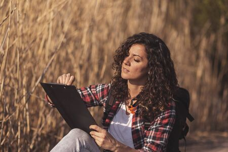 Beautiful woman enjoying an autumn day in nature, drawing landscapes in a sketchbook