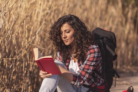 Beautiful young woman sitting on the wooden lake docks, enjoying a beautiful autumn day in nature and reading a book Stockfoto - 127979656