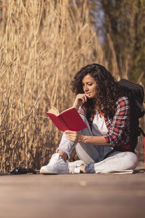 Female student sitting on the wooden lake docks, enjoying a suuny autumn day in nature and studying for an exam period
