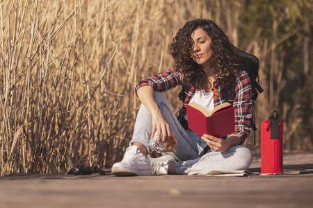 Beautiful woman sitting on the wooden docks, enjoying an autumn day in nature, reading a book and eating sandwich by the lake