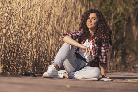 Beautiful young female backpacker sitting on the wooden lake docks, taking a break from hinking, relaxing in nature and eating a sandwich