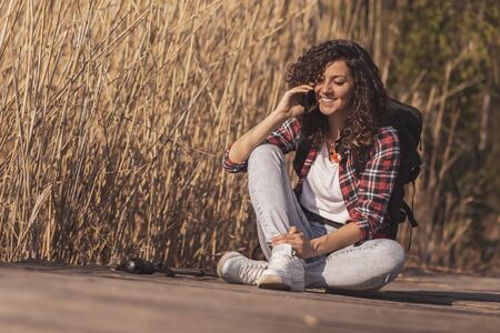 Beautiful woman sitting on the wooden lake docks, enjoying an autumn day in nature, relaxing after hiking and having a phone conversation