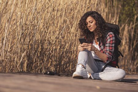 Woman sitting on the wooden lake docks, enjoying an autumn day in nature, relaxing after hiking and typing a text message on a smartphone Stockfoto - 127979659