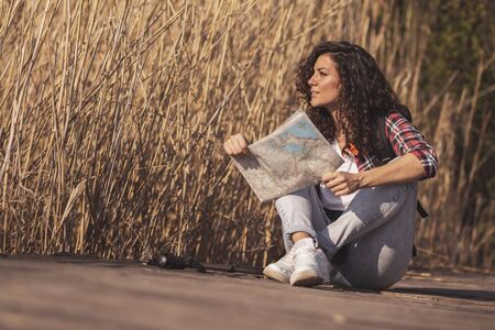 Woman sitting on the wooden lake docks, taking a break from hiking in nature, relaxing and reading a map, planning hiking route