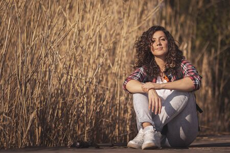 Woman sitting on the wooden lake docks, taking a break from hiking in nature, relaxing and enjoying a sunny autumn day
