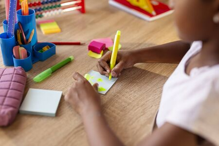 Beautiful little girl sitting at her desk, having fun writing and drawing on colorful sticky notes