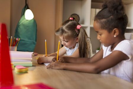 Two little girls sitting at a desk, writing in their notebooks, doing a math homework and studying for school