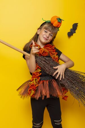 Beautiful little girl in Halloween witch costume playing a broomstick guitar and having fun on Halloween