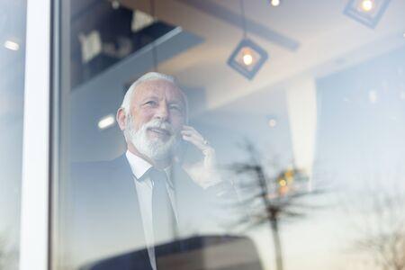 Senior businessman sitting at a restaurant table, having a phone conversation