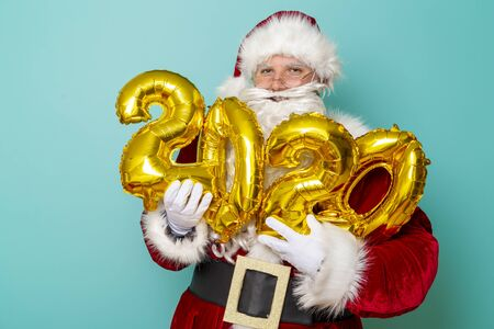 Portrait of a Santa Claus holding 2020 numbers shaped golden balloons, isolated on mint colored background Stockfoto