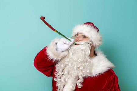 Santa Claus blowing party whistle, celebrating New Year and having fun, isolated on mint colored background Stockfoto