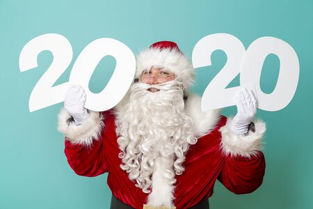 Santa Claus holding 2020 numbers isolated on mint colored background. New Years party invitation