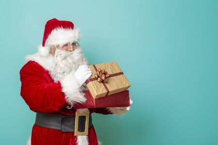 Portrait of a Santa Claus holding a nicely wrapped gift box and peeking in it, isolated on mint colored background