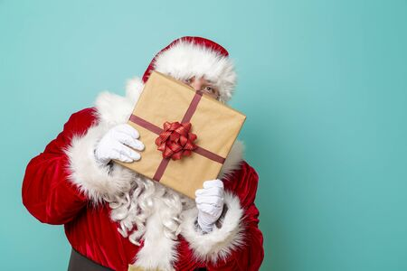 Portrait of a Santa Claus holding a nicely wrapped gift box and hiding behind it, isolated on mint colored background