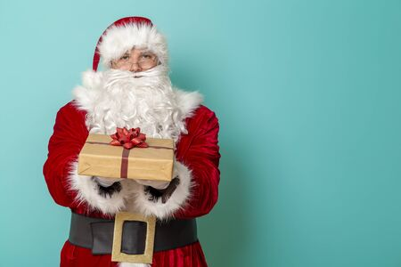 Portrait of a Santa Claus holding a nicely wrapped gift box and offering it, isolated on mint colored background Stockfoto
