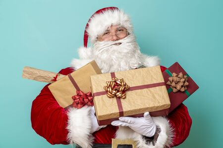 Santa Claus holding handful of presents and smiling, isolated on mint colored background