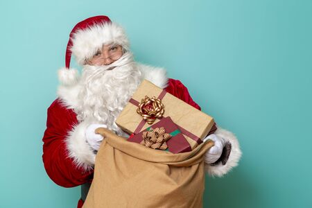 Santa Claus holding a sack full of New Year presents isolated on mint colored background