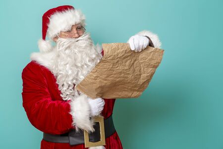 Portrait of a Santa Claus reading a letter with a list of children for New Year presents and their wish list Stockfoto