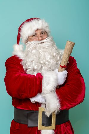 Portrait of a Santa Claus holding a letter with a list of children and their wish list for New Year presents Stock Photo