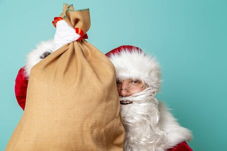 Portrait of a Santa Claus holding a sack filled with New Year presents isolated on mint colored background