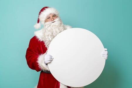 Portrait of a happy Santa Claus holding a blank cardboard circle, isolated on mint colored background. Winter sales or New Years Eve party invitation Stockfoto