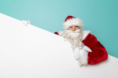Portrait of a funny Santa Claus holding a blank cardboard piece, isolated on mint colored background. Winter sales or New Years Eve party invitation