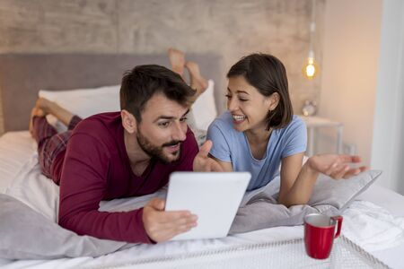 Beautiful couple lying in bed, drinking coffee and surfing the Net on a tablet computer, searching for home decor ideas