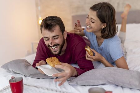 Couple in love wearing pajamas, having breakfast and coffee in bed after waking up in the morning Stockfoto