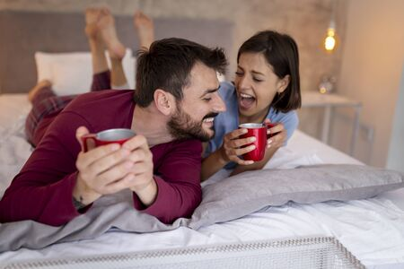 Beautiful couple in love wearing pajamas, having coffee in bed in the morning after waking up. Couple drinking coffee and having fun in bed